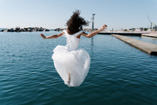 Back View Of Unrecognizable Young Female In White Wedding Dress Falling In Rippling Lake Near Pier