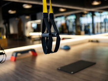Elastic TRX Ropes Hanging On Blurred Background Of Contemporary Gym During Fitness Workout