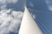 From Below Of White Contemporary Suspension Bridge With High Column Connecting Many Cables Together Against Blue Sky