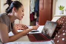 Side View Of Young Asian Female Lying On Bed And Chatting Via Video Call On Laptop With Group Of Friends While Spending Time At Home During Coronavirus Pandemic
