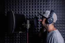Side View Of Male Singer In Headphones And Hat Standing In Acoustic Room With Soundproof Walls And Microphone And Recording Song In Studio