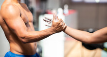 Side View Of Crop Unrecognizable Muscular Male Athlete With Naked Torso Holding Hand Of Sportswoman While Working Out In Gymnasium