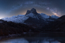 Scenery View Of Glowing Starry Dark Sky Above Snowy Mounts And Pond At Dusk During Milky Way Phenomenon