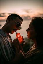 Man Lighting Cigarette For Girlfriend While Chilling On Seashore At Sunset