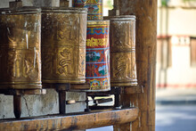Row Of Aged Shabby Buddhist Prayer Wheels In Oriental Temple In Bamei Town In China