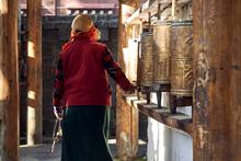 Back View Of Anonymous Woman In Stylish Clothes Turning Buddhist Golden Prayer Wheels Located In Sichuan