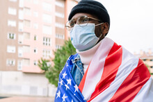 Patriotic African American Male In Medical Mask Wrapped In USA National Flag Standing On Street During Coronavirus Pandemic And Looking Away