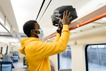 Side View Of African American Male Traveler In Medical Mask Standing In Train And Putting Backpack On Shelf Before Departure