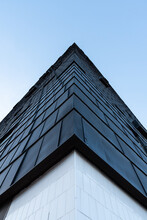 From Below Of Corner Of Contemporary Geometric Building With Black Exterior In City On Background Of Blue Cloudless Sky