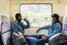 Side View Of Calm Black Men In Medical Masks Sitting On Passenger Seats And Looking Out Of Window While Traveling By Train During COVID 19 Epidemic