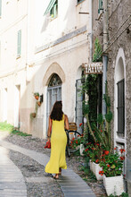 Full Body Back View Of Slim Long Haired Brunette In Bright Yellow Dress Walking Along Paved Street With Old Stone Buildings In Summer Day In City