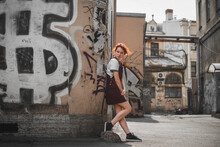 Full Body Side View Of Redhead Millennial Female In Casual Outfit Leaning Against Shabby Wall Of Aged Building With Graffiti While Standing In Old District Of Saint Petersburg In Russia