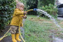 Side View Of Cute Little Child Wearing Yellow Raincoat And Rubber Boots Watering Garden From Hose After Rain