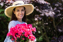 Attractive Long Haired Brunette In Summer Dress And Straw Hat Standing Near Red Blooming Bush In Garden
