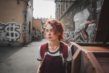 Redhead Millennial Female In Casual Outfit Leaning Against Shabby Wall Of Aged Building With Graffiti While Standing In Old District Of Saint Petersburg In Russia