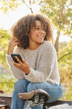 Delighted African American Female With Curly Hair In Casual Clothes Sitting On Bench Near Bicycle In Autumn Garden And Messaging With Friends On Smartphone At Weekend