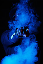 Anonymous Stylish Male Showing Fist With Rings In Shape Of Skull And Covering Face In Cloud Of Smoke Illuminated By Blue Neon Light In Dark Studio