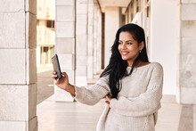 Happy Ethnic Woman Taking Selfie While Standing In Marble Passage Outside Building