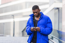 African American Male In Warm Jacket Standing On Street Near Building And Messaging On Social Media Via Smartphone
