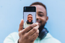 Low Angle Cheerful Adult Black Hipster Guy In Casual Outfit With Headphones On Neck Taking Self Portrait On Mobile Phone Against Blue Background
