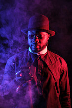 Confident African American Male In Stylish Outfit And Sunglasses Smoking Vape And Exhaling Steam In Studio With Neon Lights While Using Smartphone