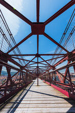 From Below Of Bridge With Wooden Planks And Metal Beams Between Grid Fences Under Blue Cloudy Sky