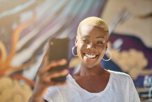 Smiling African American Female With Short Hair Taking Self Portrait On Smartphone Camera In Cafe
