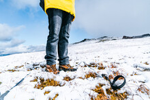 Low Angle Of Legs Of Crop Hiker In Warm Clothes Standing On Snowy Slope In Pyrenees Mountains On Sunny Day In Andorra