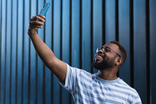 Low Angle Cheerful Adult Black Hipster Guy In Casual Outfit Taking Self Portrait On Mobile Phone Against Blue Background
