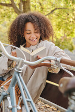 Calm African American Female With Curly Hair Sitting On Bench Near Bicycle In Autumn Park And Enjoying Interesting Story In Book