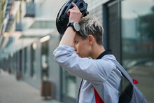 Young Woman Cyclist Puts On Helmet While Standing Next To Modern Building On Summer Day In City, Side View