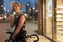 Young Woman Talking On Phone Near Store And Bike At Night City