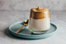Tasty Cold Dalgona Coffee In Glass Served On Blue Plate On Concrete Table
