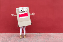 Unrecognizable Playful Kid Wearing Funny Costume Of Monster Made Of Carton Box Standing On Street During Holiday Celebration