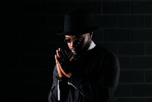 Determined African American Male Wearing Round Sunglasses And Trendy Black Clothes Standing On Dark Background In Studio And Looking Away