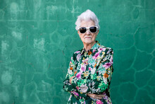 Confident Senior Gray Haired Female In Stylish Colorful Clothes And Trendy Sunglasses Smiling Happily While Standing Against Green Wall Looking At Camera