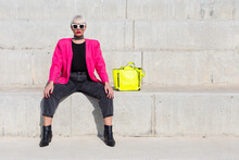 Confident Female Model Wearing Bright Pink Jacket Sitting On Stairs With Vivid Yellow Handbag In City And Looking At Camera