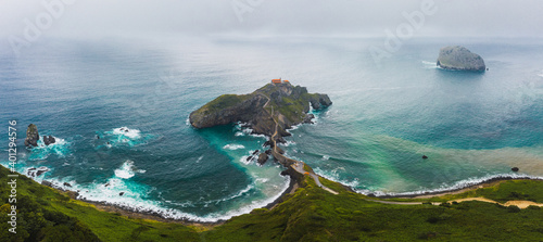 Drone view of paving stone way leading along stone bridge and ridge of rocky hill to lonely house on island Gaztelugatxe surrounded by tranquil sea water under cloudy sky in Basque Country