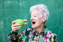 Stylish Elderly Female In Trendy Outfit Holding Green Apple With Denture While Standing Against Green Background
