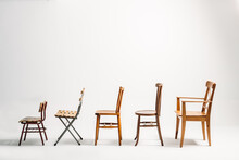 Profile Of Five Old Wooden Chairs Against White Background