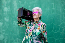 Cool Elderly Female In Colorful Trendy Blouse And Sunglasses Carrying Record Player And Enjoying Music Against Green Wall