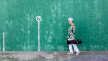 Full Body Side View Of Happy Elderly Gray Haired Female In Stylish Outfit Carrying Record Player On Shoulder While Standing Against Green Wall On Street