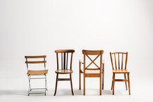 Four Classical Wooden Chairs Against White Background