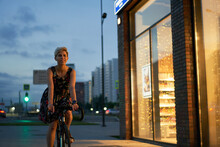 Woman In Dress Rides Bicycle In Night City Near Store