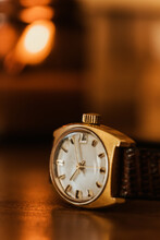 Closeup Of Old Fashioned Mechanical Wristwatch With Shiny Golden Case Placed On Wooden Table Against Blurred Interior Background