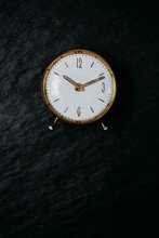 From Above Of Retro Round Clock With Yellow Metal Case And Missing Number On Dial Placed On Black Background