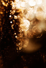 Shiny Golden Sparkling Abstract Background And Texture Of Blurred Glowing Lights In Darkness