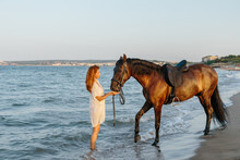 Woman In White Dress Caressing Her Horse On The Seashore At Sunset