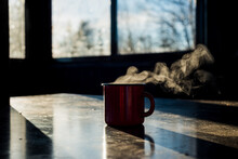 A Red Coffee Mug Sits On The Table, Steaming