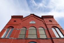 Straight On View Looking Up Of An Old Red Brick Church With Arched Windows, Blue Sky Copy Space, Horizontal Aspect